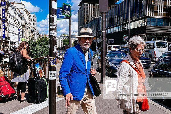 Elegant and fashinable senior couple walking on street and next to them young women carrying big luggage to their hotel  Paris  Île-de-France  France.