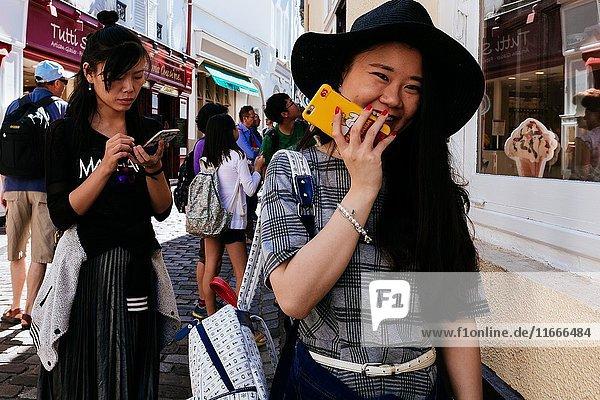 Pretty japanese tourists playing with mobile phones on street. Montmartre  Paris  Île-de-France  France