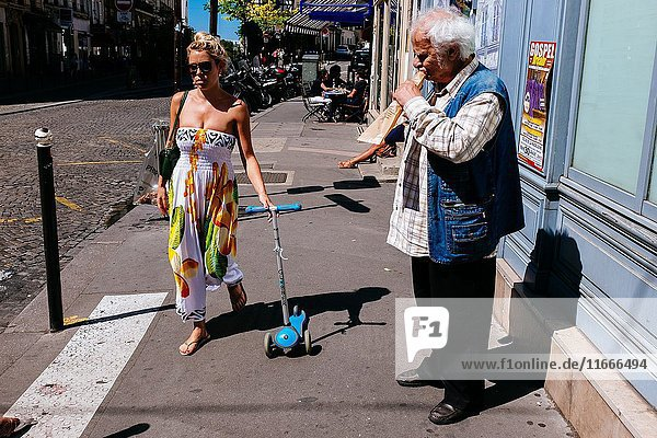 Pretty young woman walking on street dragging scooter passing in front of man eating baguette bread. Montmartre  Paris  Île-de-France  France