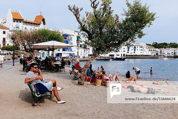 People sunbathing on beach while others are walking on promenade. Cadaqués  Alt Amporda  Gerona  Catalonia  France.