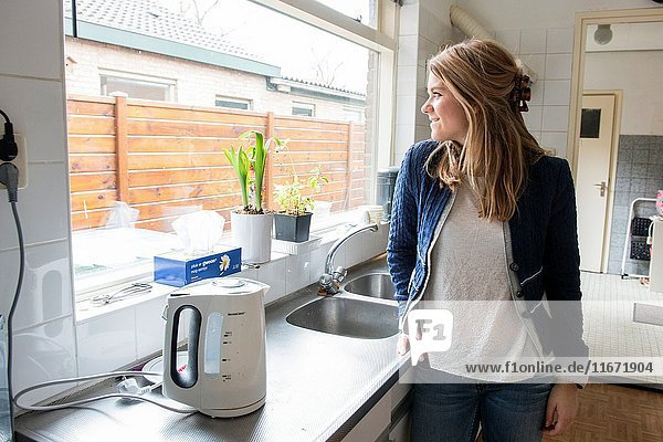 Tilburg  Netherlands. Young caucasian woman relaxing a moment at her kitchen sink after doing some home cleaning.
