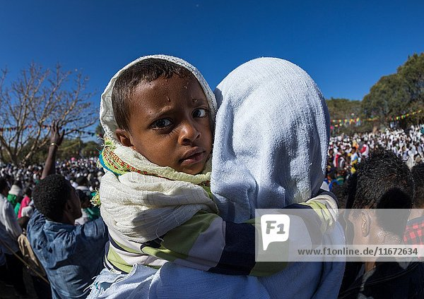 Ethiopian mother holding her wet son after taking the holy bath during Timkat epiphany festival  Amhara region  Lalibela  Ethiopia.