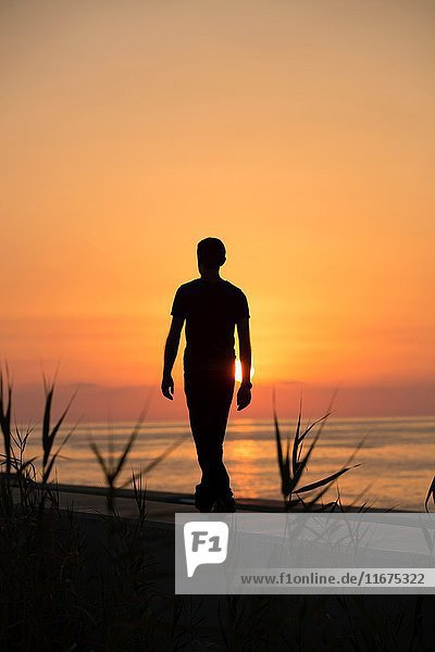 Full length silhouette of a male figure walking on the beach at sunset.