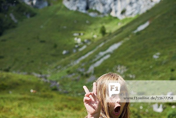 Young female child showing peace sign during hiking adventure in Bavarian mountains  Brauneck