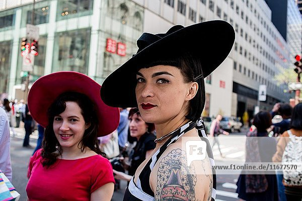 New York  NY - April 16  2017. A tattooed woman wears a jaunty black hat at New York's annual Easter Bonnet Parade and Festival on Fifth Avenue. The tattoo is of a perfume bottle labelled 'Oo-la-la. '.