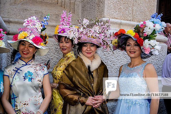 New York  NY - April 16  2017. A group of Asian women in elaborate hats on the steps of St. Patrick's Cathedral at New York's annual Easter Bonnet Parade and Festival on Fifth Avenue.
