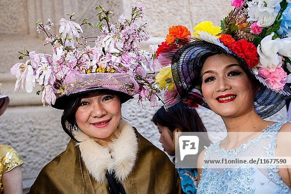 New York  NY - April 16  2017. Two Asian women in elaborate hats on the steps of St. Patrick's Cathedral at New York's annual Easter Bonnet Parade and Festival on Fifth Avenue.