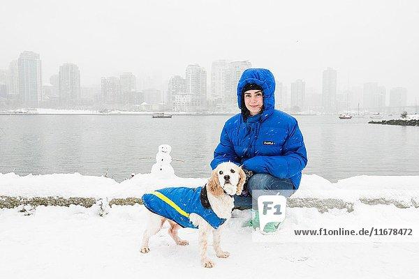 A woman and dog at Alder Bay  off False Creek  Vancouver  BC  Canada.