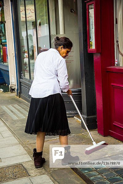 Cleaning lady sweeping with broom in front of the entrance of a building
