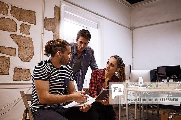 Team of three young sales representatives in a strategic meeting looking at one of the guys explaining a new strategy.