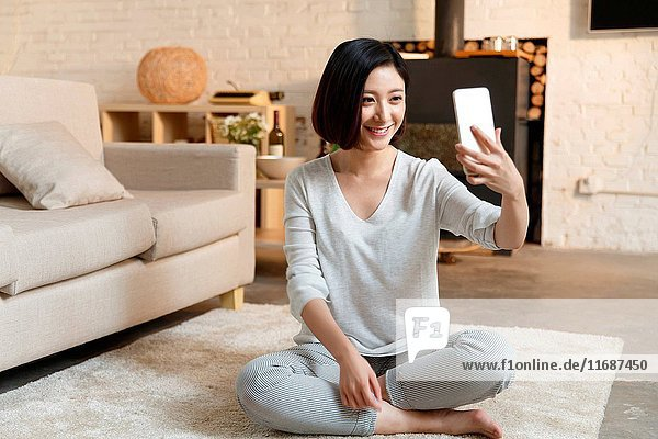 Young woman taking self portrait with cell phone