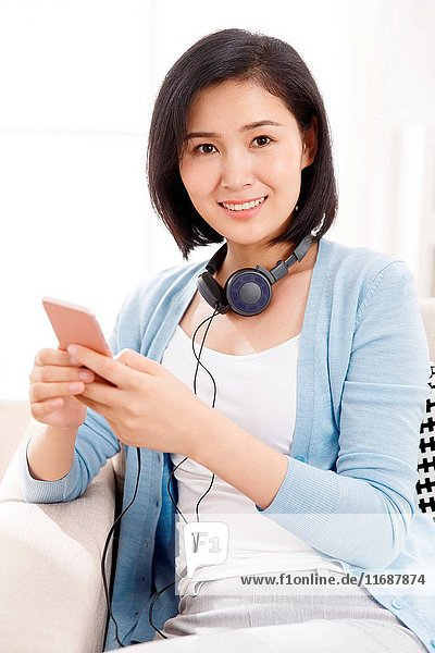 Woman using phone with headphones