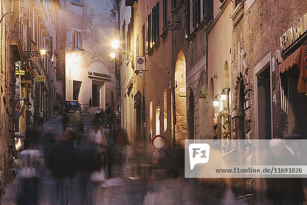A busy street at night in the Tuscan hill town of Montepulciano.
