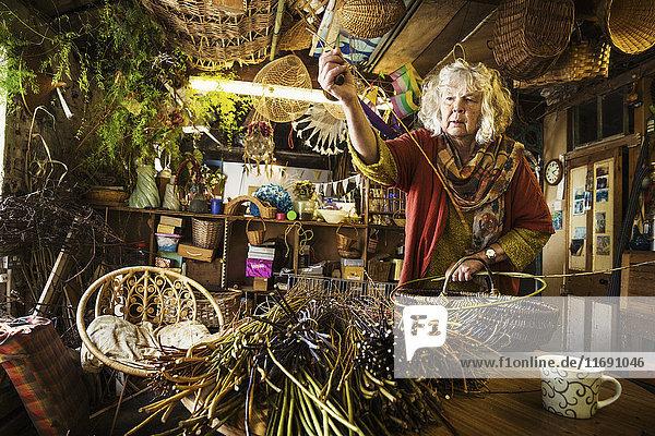 Frau webt einen Korb in einer Weberei. Frau webt einen Korb in einer Weberei.
