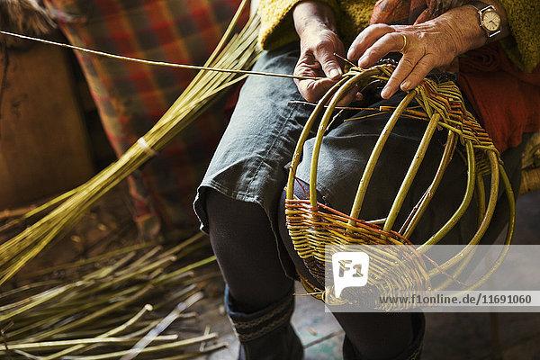 Nahaufnahme einer Frau  die in der Weberei einen Korb webt. Nahaufnahme einer Frau, die in der Weberei einen Korb webt.