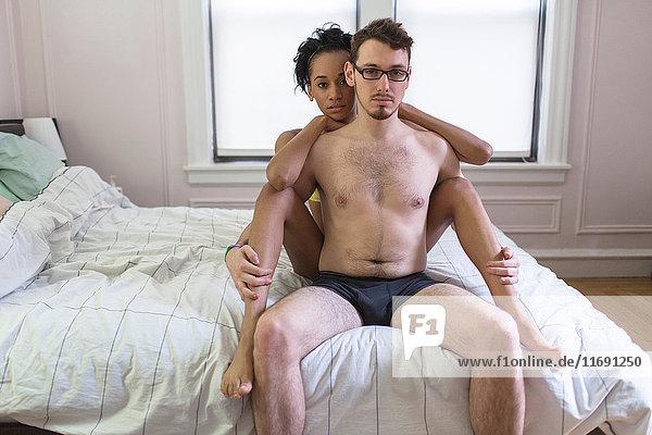 Junges Paar sitzt auf dem Bett und trägt Unterwäsche