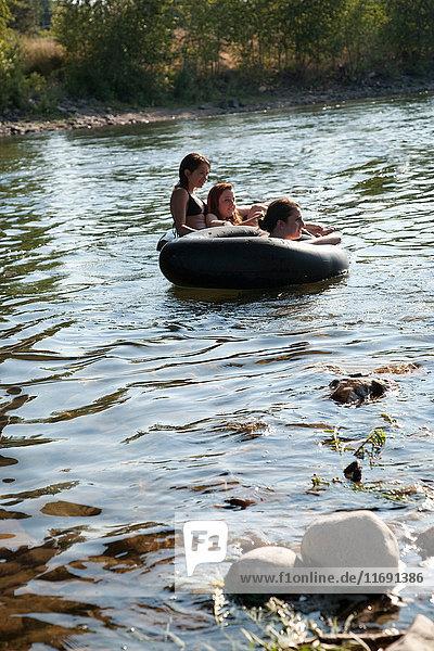 Damen fahren in Gummiflößen auf dem Fluss