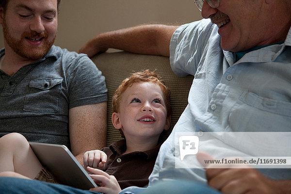 Junge zeigt dem Großvater ein digitales Tablett