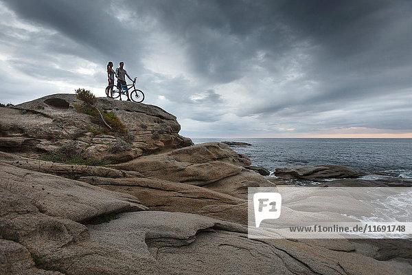 Auf einem Felsblock am Meer stehendes Ehepaar