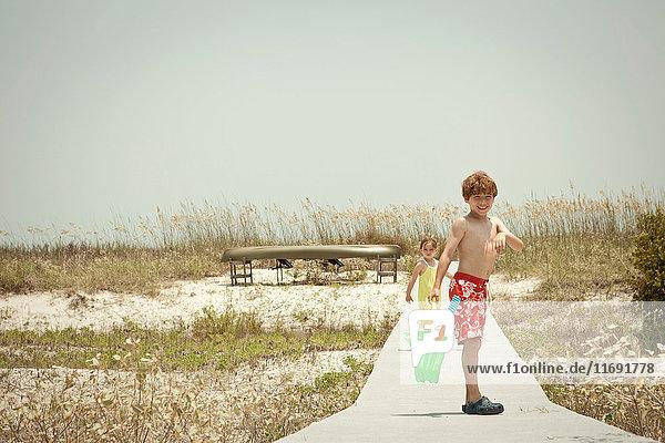 Kinder auf Holzsteg am Strand