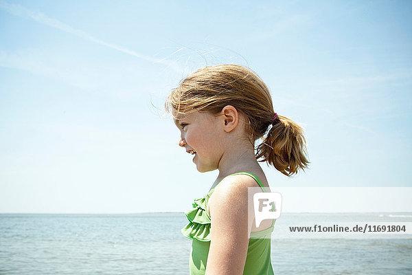 Lächelndes Mädchen steht am Strand