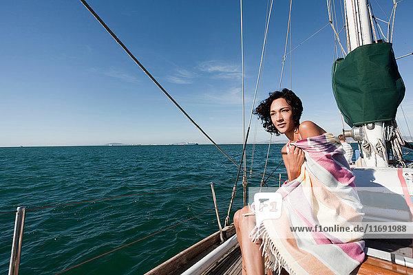 Junge Frau auf Jacht in Decke gehüllt