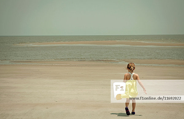 Mädchen trägt Schaufel und Eimer am Strand