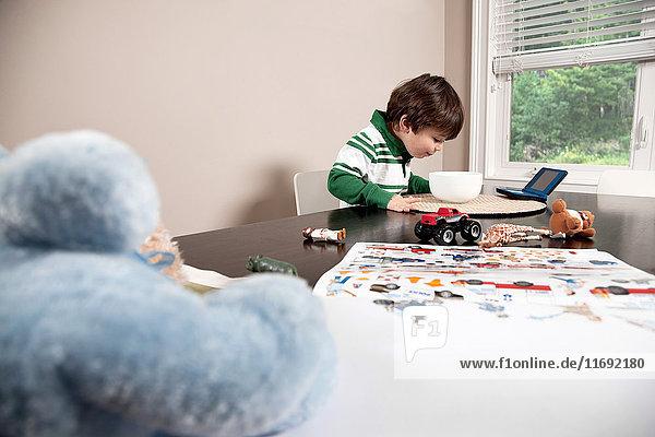 Junge bei Tisch mit Schüssel voller Essen und Spielzeug