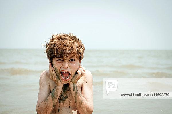 Junge spielt mit nassem Sand am Strand