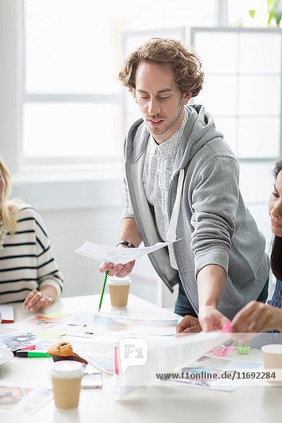 Junger Mann zeigt Pläne bei Treffen im Kreativbüro