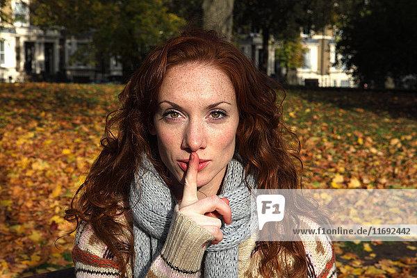 Frau hält im Park den Finger über die Lippen