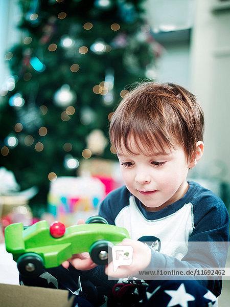 Junge öffnet Weihnachtsgeschenke