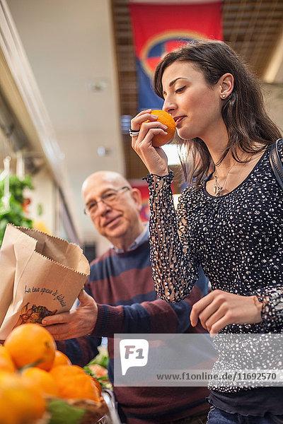 Frau riecht frische Orangen auf dem Markt