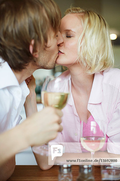 Couple kissing at dinner table