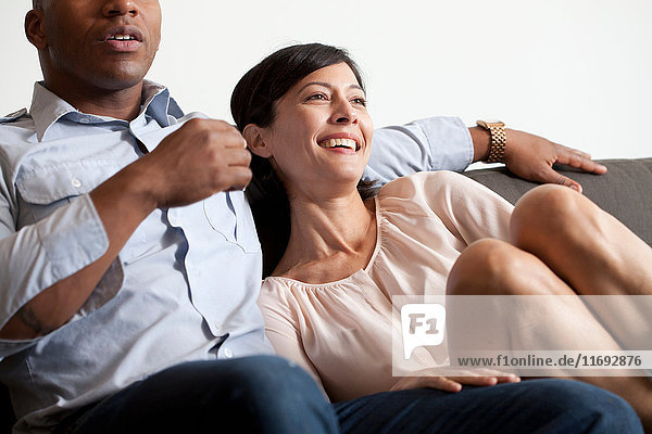 Paar entspannt auf dem Sofa  lächelnd