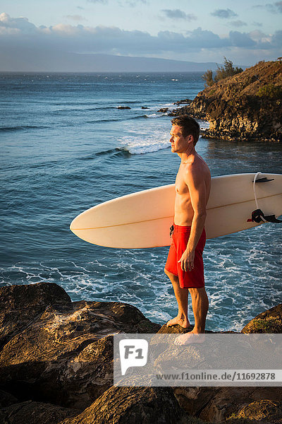 Surfer carrying board on beach