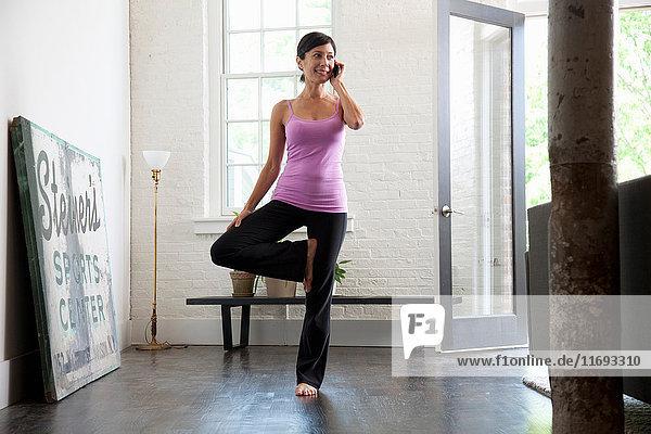 Reife Frau  die ein Mobiltelefon benutzt und eine Yogastellung einnimmt