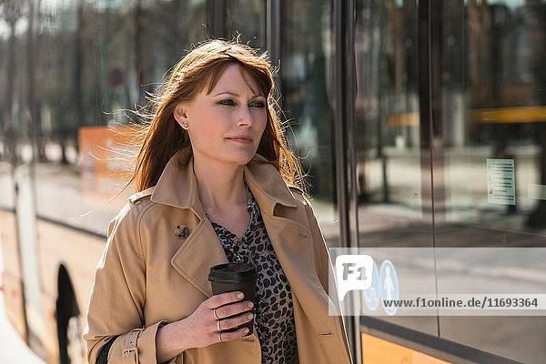 Frau mit Kaffee zum Mitnehmen neben dem Stadtbus