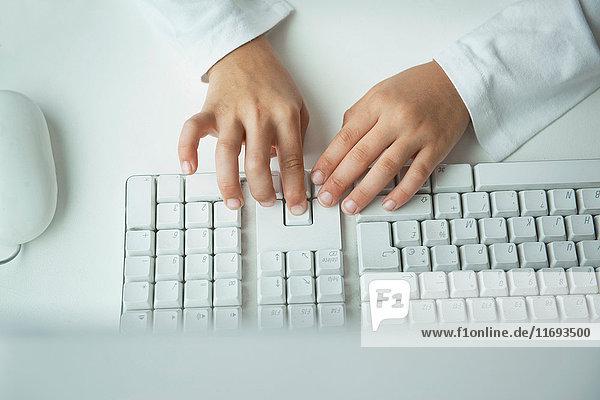Kind tippt auf der Computertastatur