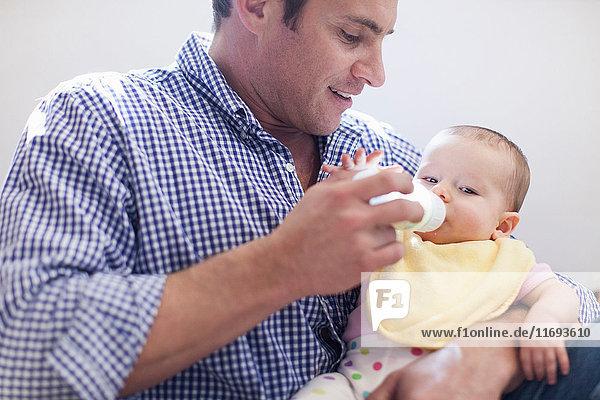 Vater füttert Baby-Tochter-Flasche