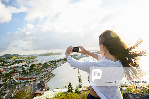 Woman taking picture of coast landscape