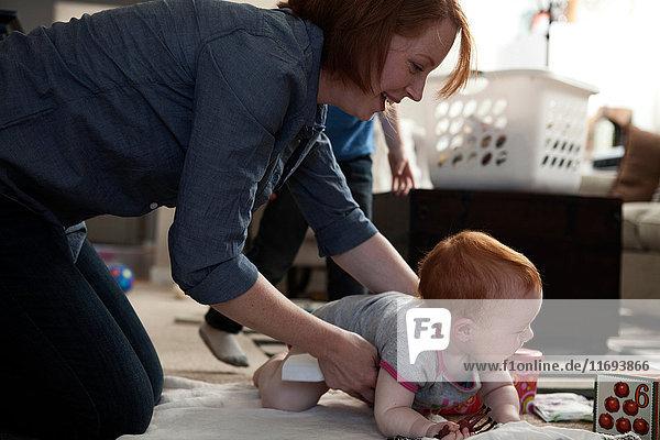 Mutter und kleine Tochter spielen auf dem Boden
