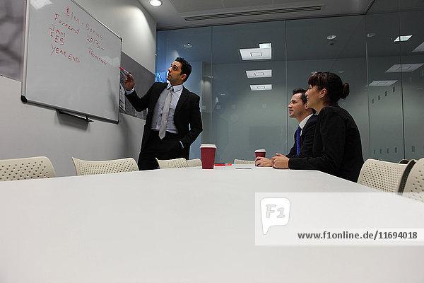Geschäftsmann benutzt Whiteboard bei Besprechung