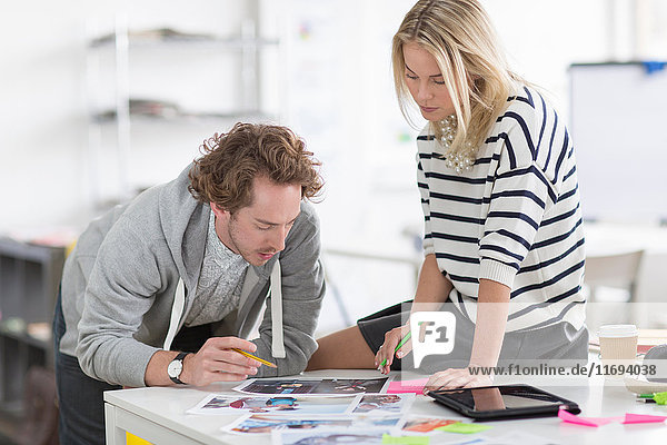 Colleagues discussing photographs on desk in creative office