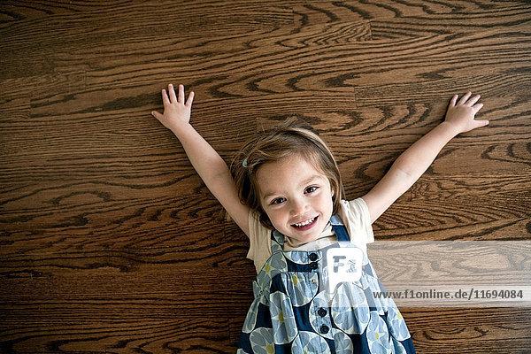 Kleines Mädchen auf Holzboden liegend
