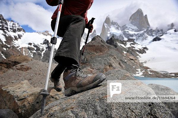 Frau macht einen Schritt mit Trekkingstöcken am Aussichtspunkt Monte Fitz Roy im Nationalpark Los Glaciares,  El Chalten,  Argentinien