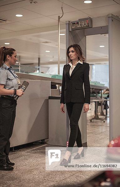 Sicherheitsbeamter kontrolliert weiblichen Passagier bei der Flughafensicherheit