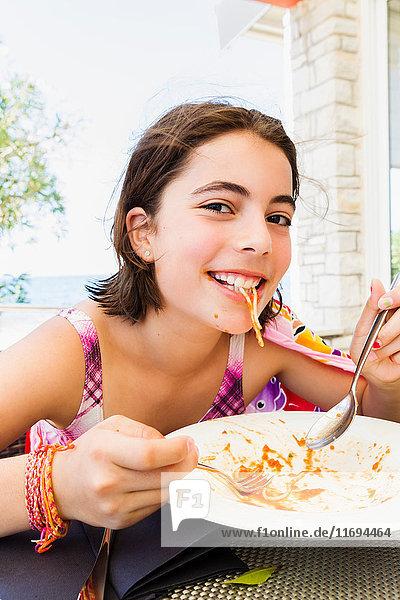 Lächelndes Mädchen isst Nudeln im Freien