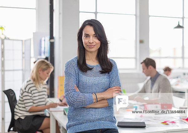 Mittelgroße erwachsene Frau sitzt auf dem Schreibtisch und lächelt im kreativen Büro  Porträt