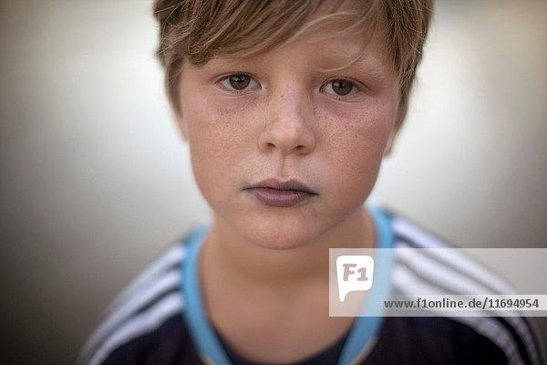 Nahaufnahme eines in die Kamera blickenden Jungen mit blau gefärbten Lippen